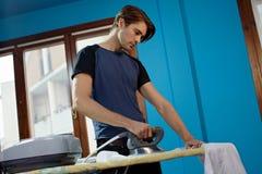 Man with iron doing chores Stock Photos