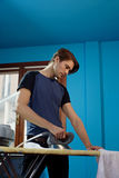 Man with iron doing chores Stock Images