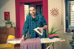 Man with iron on ironing board  in living room royalty free stock images