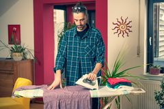 Man with iron on ironing board  in living room stock photo