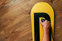 Man ironed wax on a snowboard, lying   wooden floor Royalty Free Stock Photo