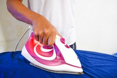 Man ironing blue shirt royalty free stock image