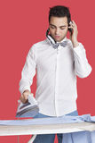 Man ironing cloth while listening music over red background Stock Photos