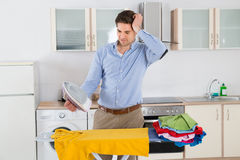 Man Ironing Clothes With Electric Iron Stock Image