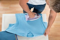 Man Ironing Clothes At Home Stock Photos