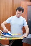 Man ironing his pants Stock Image