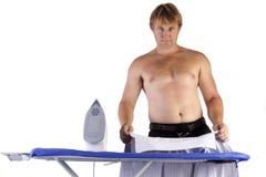 Man ironing his work shirt Stock Photography