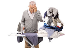 Man ironing and holding his head in disbelief Stock Photos