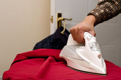 Man ironing a red shirt. Mans arm is seeing ironing a red shirt Royalty Free Stock Image