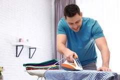 Man ironing shirt on board at home royalty free stock images
