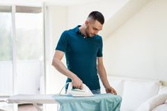 Man ironing shirt by iron at home. Housework and household concept - man ironing shirt on iron board at home royalty free stock photography