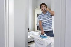 Man Ironing Shirt White Using Cell Phone Royalty Free Stock Images