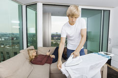 Man ironing shirt while woman relaxing on sofa at home Royalty Free Stock Photography
