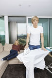 Man ironing shirt while woman sitting on sofa at home Royalty Free Stock Photo