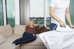 Man ironing shirt while woman sitting on sofa at home Stock Photography