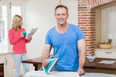 Man ironing while wife reading the news Stock Photo