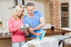 Man ironing while wife reading the news Stock Photos