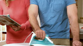 Man ironing while woman reading stock video footage