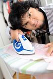 Man ironing. Young asian man unhappy during ironing his shirt Royalty Free Stock Photography