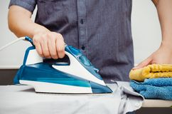 Man irons clothes on ironing board with blue iron Stock Photos