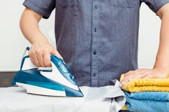 Man irons clothes on ironing board with blue iron Royalty Free Stock Photos