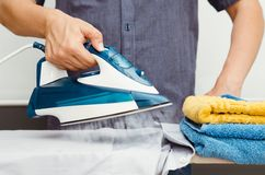 Man irons clothes on ironing board with steaming iron Royalty Free Stock Photos
