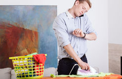 Man irons clothes and looks at his watch Royalty Free Stock Image