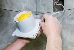 Free Man Is Installing The Wall Bathroom Fan Vent. Restoration Process. Wires In Hands Stock Image - 180147421