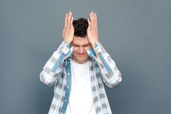Man isolated on gray wall free style standing holding head having migrain stock photography