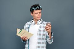 Man on gray wall tourism concept standing holding dictionary using translator application on smartphone stock image