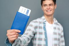 Man isolated on gray wall tourism concept standing holding passport with ticket close-up smiling blurred royalty free stock photography