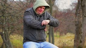 Man with itchy body at outdoors on the bench in the park stock footage