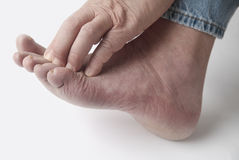 Man with itchy toes. A man scratches his irritated toes Royalty Free Stock Photography
