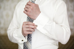 Man in ivory shirt and tie puts on cufflink. Stock Photo