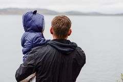 A man in a jacket with a child in his arms stands on the lake, back to the camera, in the spring royalty free stock photo