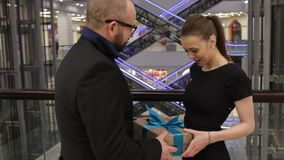 Man in a jacket is giving gift to young woman and she hug him in store indoor. She is smiling stock footage