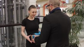 Man in a jacket is giving gift to young woman and she hug him in store indoor. She is smiling stock video
