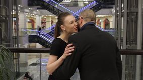 Man in a jacket is giving gift to young woman and she hug him in store indoor. She is smiling stock video footage
