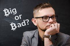 Man in a jacket and glasses on the background of black school board on which it is written Big or Bad?. Man in a jacket and glasses on the background of a black royalty free stock photo