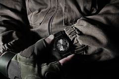 Man in jacket and gloves holding military watch royalty free stock images