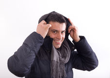 Man in jacket with hood. Attractive young man in winter jacket with scarf putting hood on head. Isolated on white background Royalty Free Stock Photos