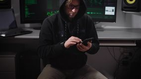 A man in a jacket with a hood in the computer room. A hacker in sunglasses and with a smartphone on hand sitting on a stock video