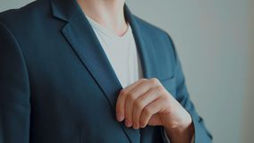 A man in a jacket on a light background, a groom`s fees.  stock video footage