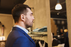 Man in jacket looking to mirror at clothing store Royalty Free Stock Photos