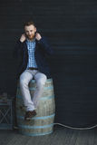 Man in a jacket. Sitting on a barrel Royalty Free Stock Photo