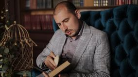 A man in a jacket sitting on the couch in the background of the bookcase and reading a book. A solid man in a jacket reading a book while sitting on the couch stock video