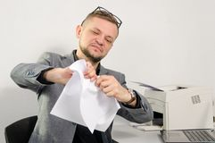 A man in a jacket is wrinkling documents in his hands at the off. Ice Royalty Free Stock Photos