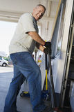 Man Jacking Up Vehicle In Service Station Royalty Free Stock Photography