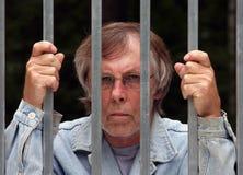 Man in jail. Main in jail looking through bars Stock Photos