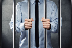 Man in jail. Young corrupted businessman behind the prison bars Stock Image